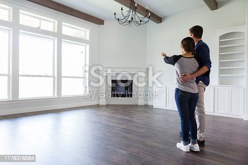 Rear view of a young couple planning the decor in the living room in their new home.