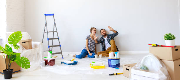 Young couple planning room interior Young couple woman and boyfriend pointing away  while sitting near white wall and planning room interior during renovation in new apartment home improvement stock pictures, royalty-free photos & images