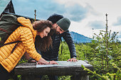 Young couple in the woods planning trip. Using map