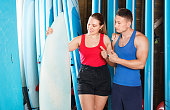 Young smiling  positive couple planning to surf, choosing boards and surfing suits in beach club