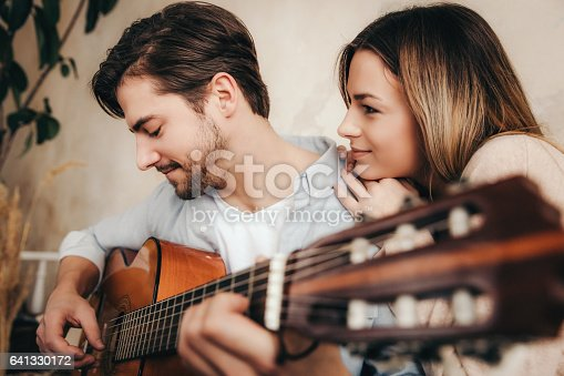 istock young couple playing acoustic guitar 641330172