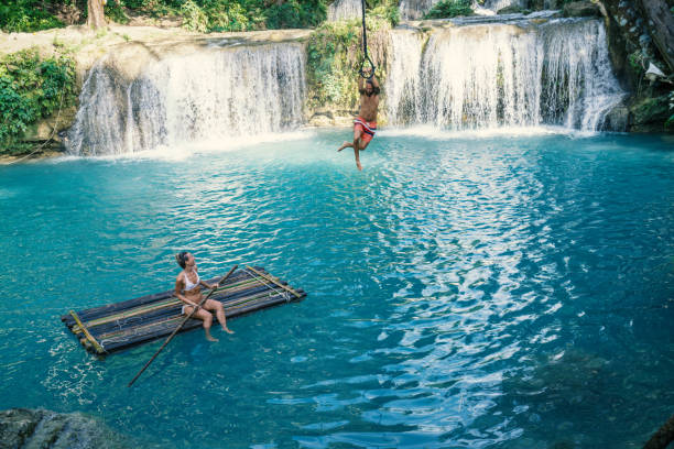 young couple playing at beautiful waterfall in the philippines - philippines stock photos and pictures