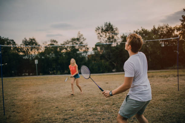 Young Couple Playing Badminton in the Park Young couple playing badminton in the park in Melbourne, Australia. badminton stock pictures, royalty-free photos & images