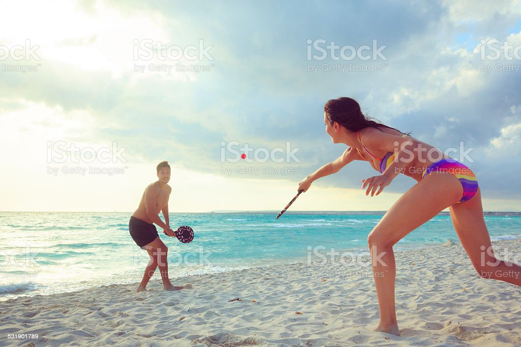 young couple playing beach tennis stock photo