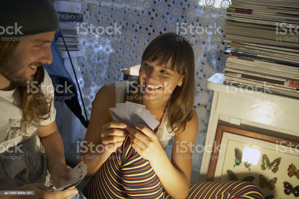 Young couple playing cards, smiling royalty-free stock photo