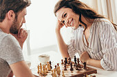 young couple playing chess while sitting at table at home