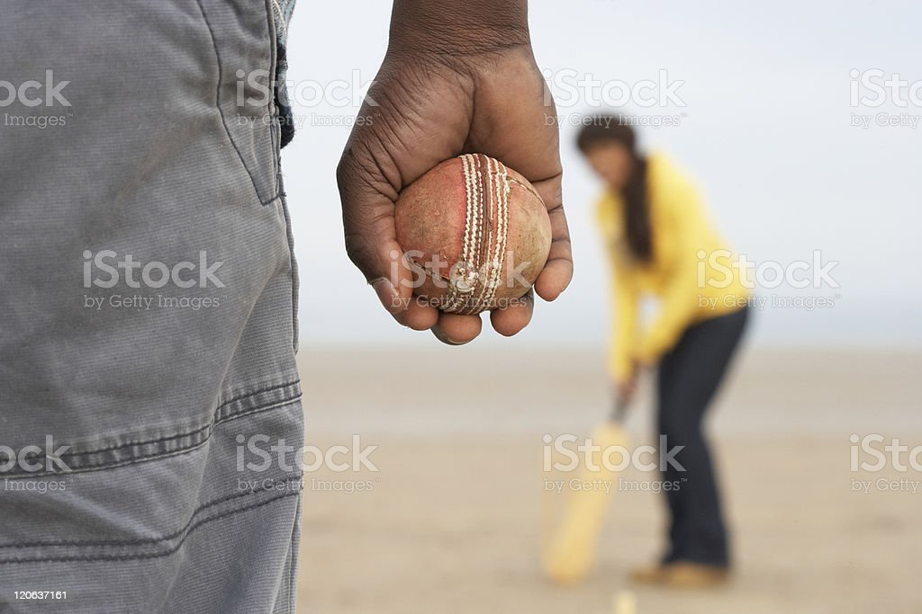 Young Couple Playing Cricket On Beach Holiday stock photo