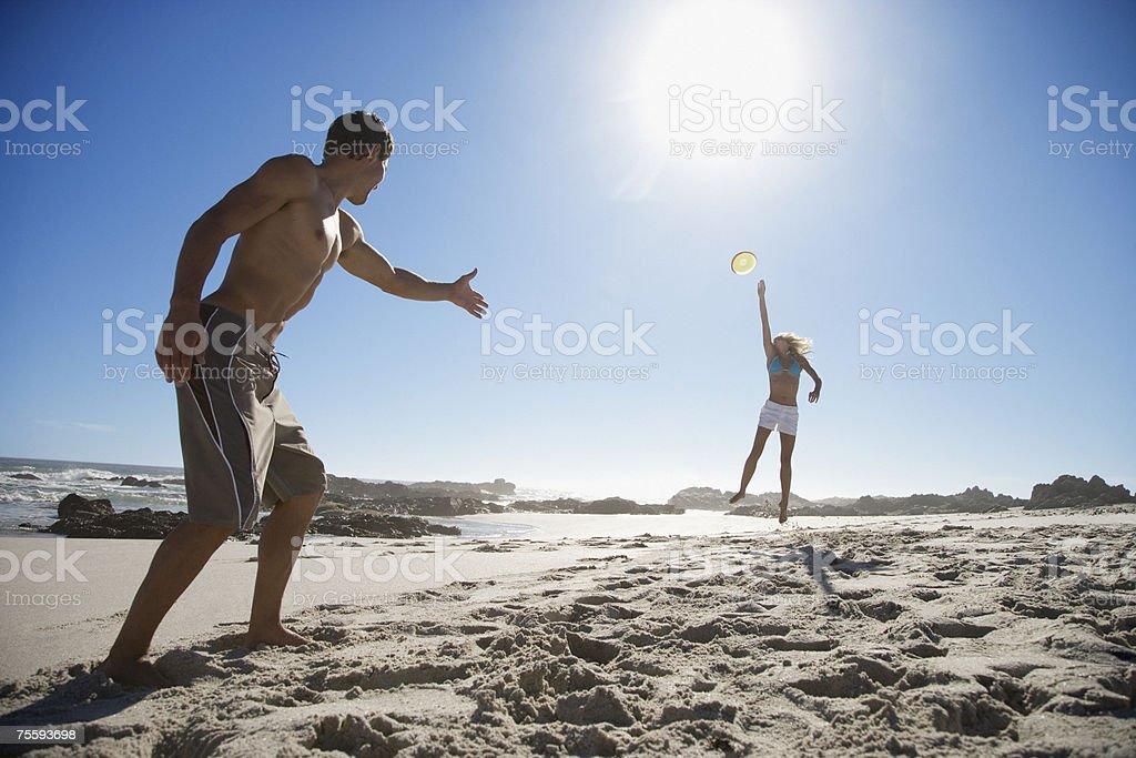 Um jovem Casal Jogando Disco voador na praia foto de stock royalty-free