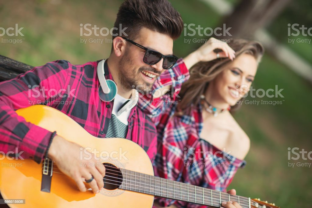 Young couple playing guitar at the park royaltyfri bildbanksbilder