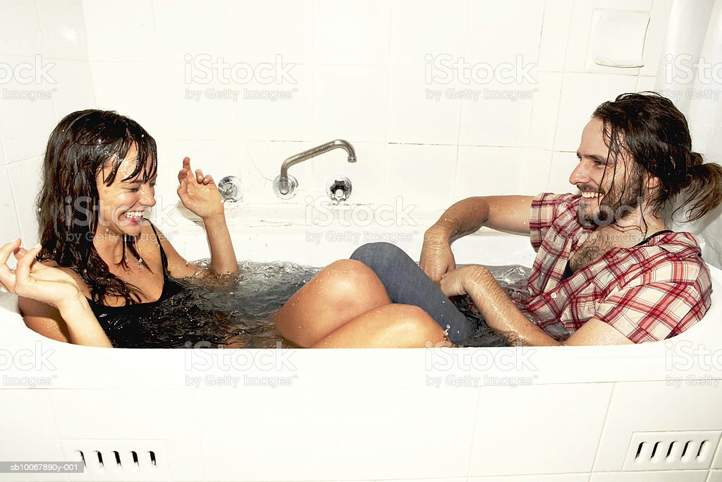 Young couple playing in bath tub, smiling, side view 免版稅 stock photo