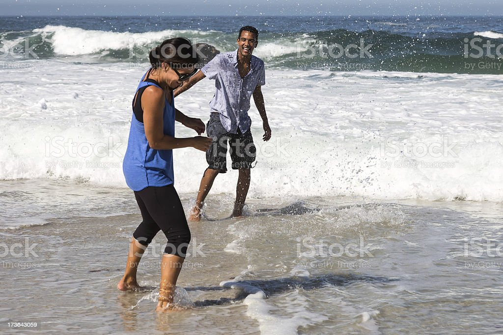 Young Couple Playing in the Water on Beach stock photo