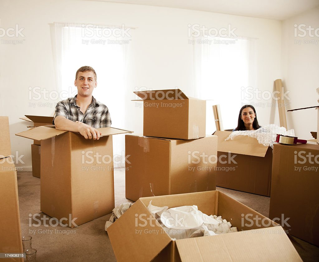 A couple play inside moving boxes.