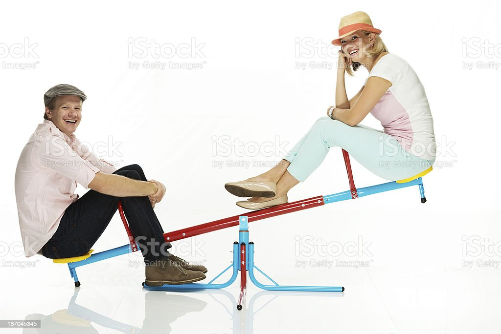 Young couple playing on the seesaw royalty-free stock photo