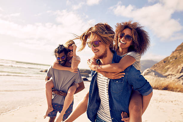 Young couple playing piggyback on beach stock photo