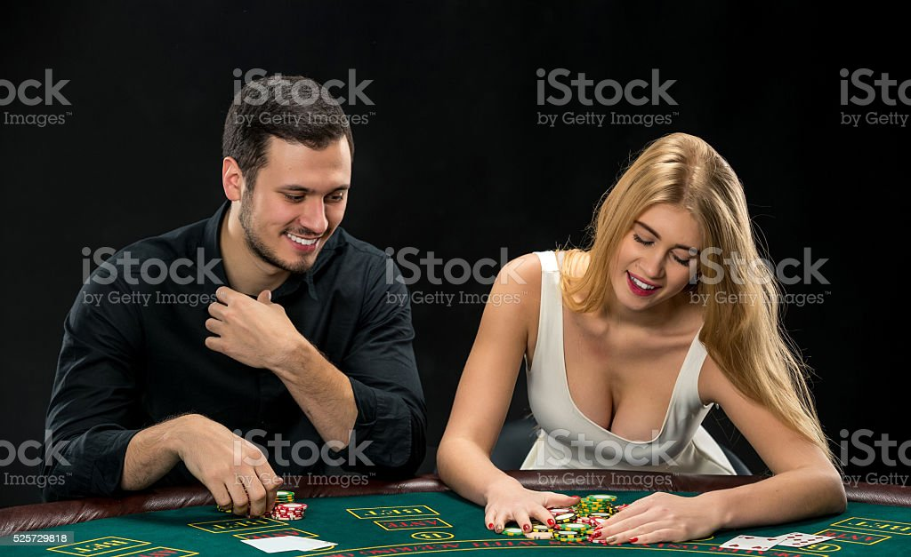 Young couple playing poker, woman taking poker chips after winning stock photo
