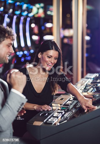 istock Young couple playing slot machines at the Casino 528473796
