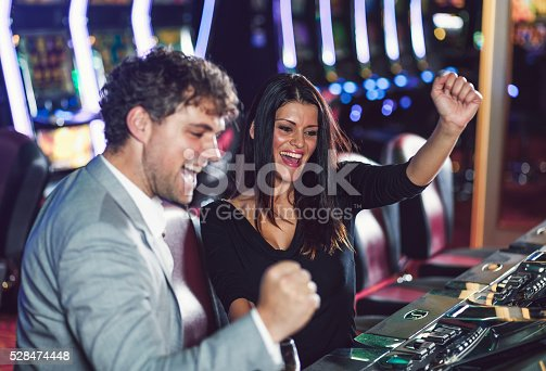 istock Young couple playing slot machines at the Casino 528474448