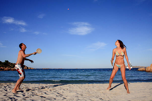 Young couple playing tennis on a beach. stock photo