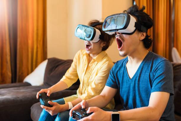 仮想現実ゲームを一緒に遊ぶ若いカップル - ゲーム ヘッドフォン ストックフォトと画像
