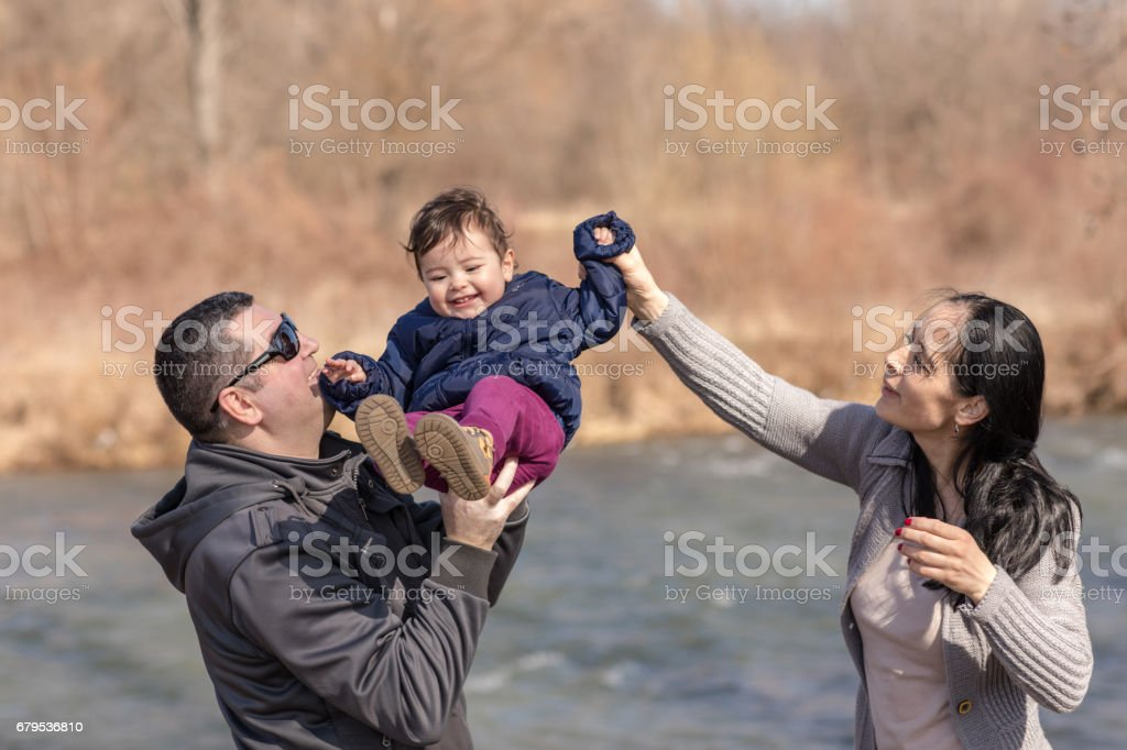 Young couple playing with baby daughter on riverside stock photo