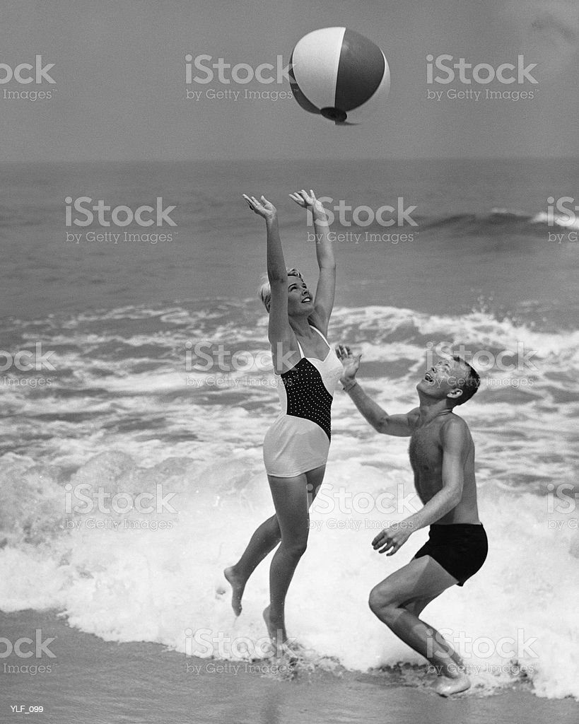 Young couple playing with beach ball at water's edge royalty free stockfoto