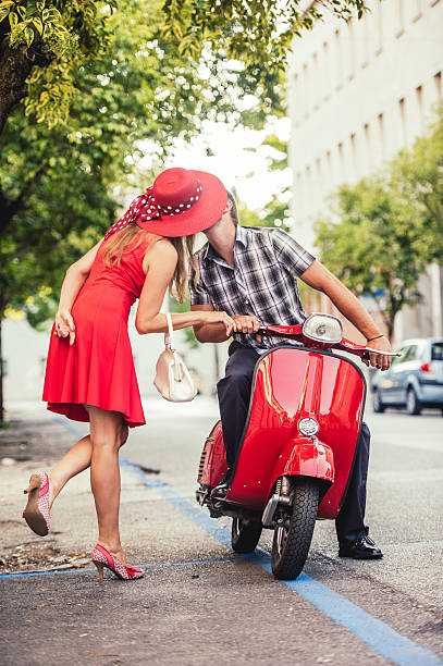 young couple portrait with a vintage scooter - red hutgesellschaft stock-fotos und bilder