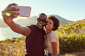 Young Couple Pose For Holiday Selfie On Clifftop