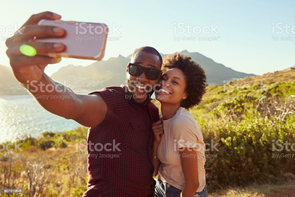 Young Couple Pose For Holiday Selfie On Clifftop stock photo