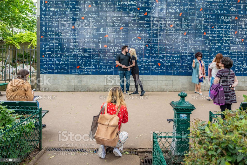 A young couple posing at the I Love You wall in Montmartre in Paris stock photo
