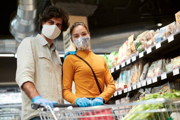 Ein junges Paar posiert für die Kamera im Supermarkt mit Gesichtsmasken. – Foto