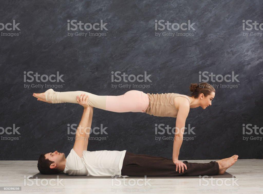 Junges Paar Acroyoga auf Matte zusammen üben – Foto