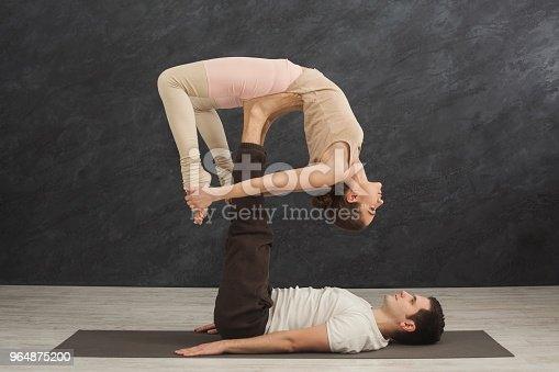 Young Couple Practicing Acroyoga On Mat Together Stock Photo & More Pictures of Acroyoga