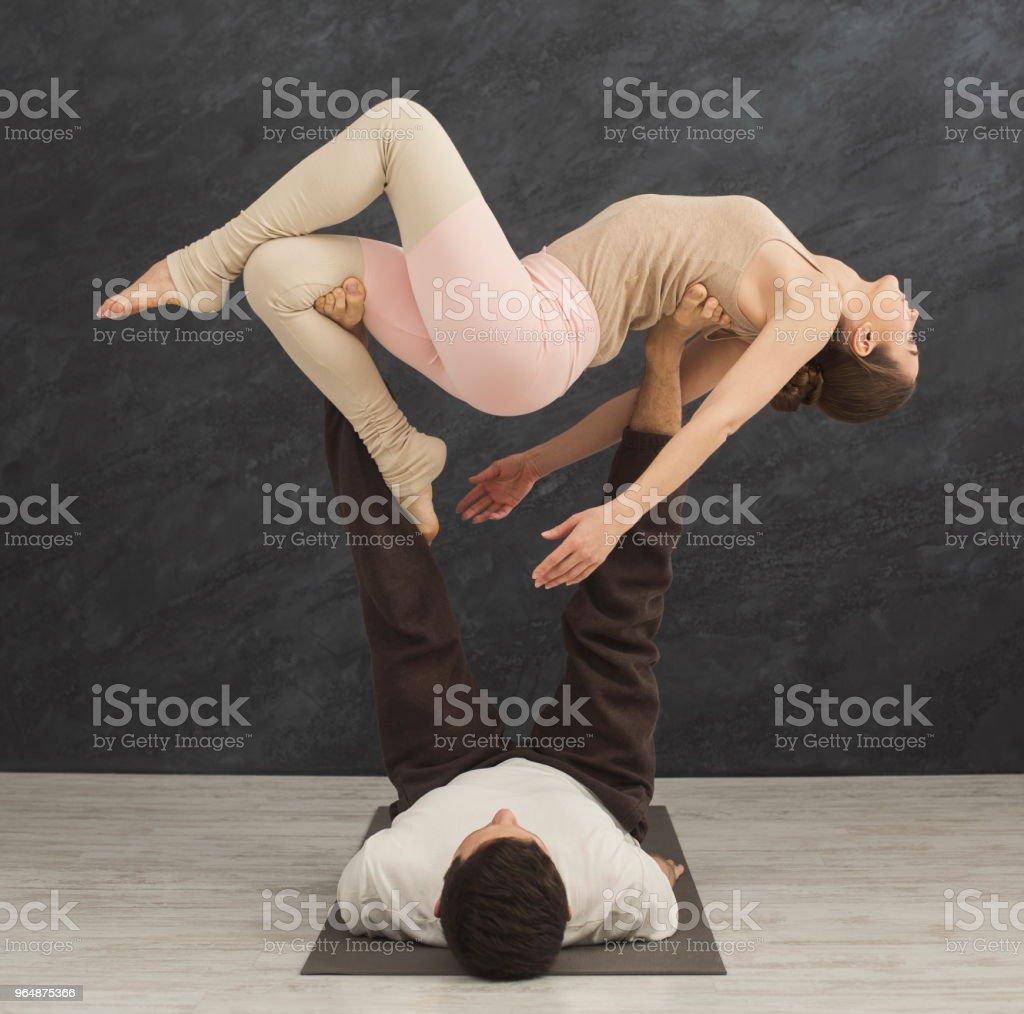 年輕夫婦在墊子上練習 acroyoga - 免版稅一起圖庫照片