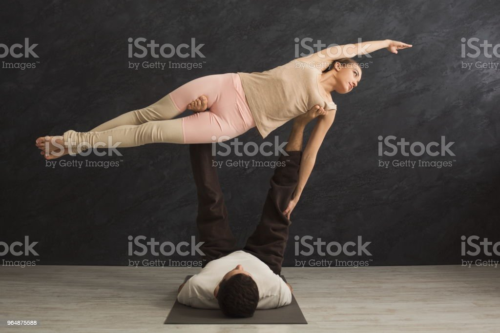 Young couple practicing acroyoga on mat together royalty-free stock photo