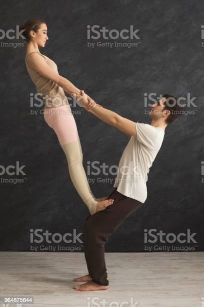 年輕夫婦在墊子上練習 Acroyoga 照片檔及更多 一起 照片