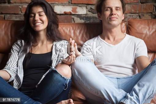916126642 istock photo Young couple practicing yoga meditating together at home on sofa 917874776