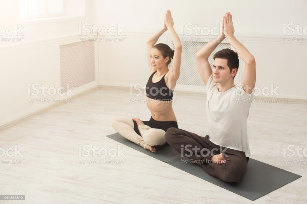 Young couple practicing yoga sitting in padmasana royalty-free stock photo