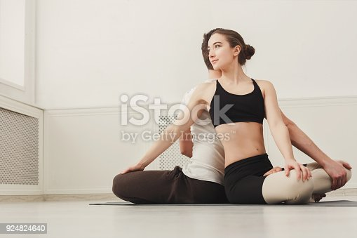 1060280760 istock photo Young couple practicing yoga together in gym 924824640