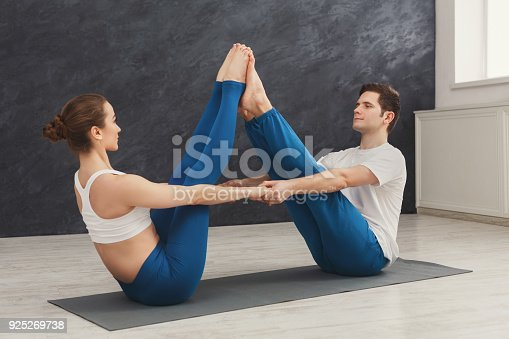 1060280760 istock photo Young couple practicing yoga together in gym 925269738