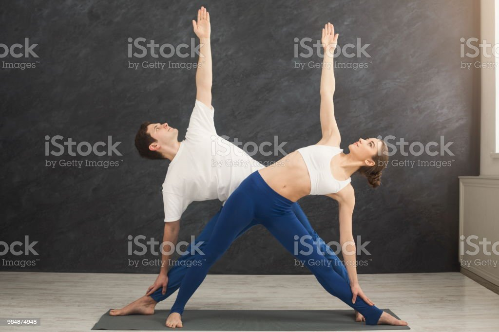 年輕夫婦一起練習瑜伽在健身房 - 免版稅一起圖庫照片