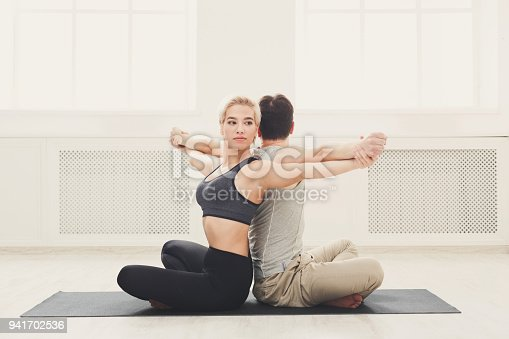 1060280760 istock photo Young couple practicing yoga together in studio 941702536