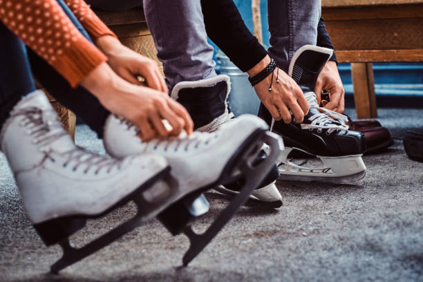 Young couple preparing to a skating. Close-up photo of their hands tying shoelaces of ice hockey skates in the locker room Young couple preparing to a skating. Close-up photo of their hands tying shoelaces of ice hockey skates in a locker room ice rink stock pictures, royalty-free photos & images