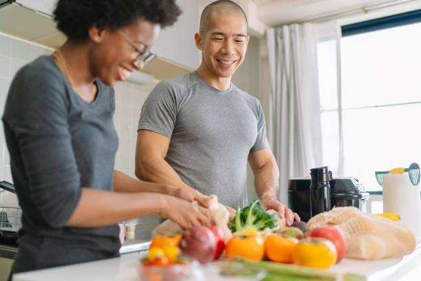 giovane coppia che prepara cibo vegano a casa - grocery home foto e immagini stock