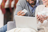 Young couple purchase Christmas gifts online