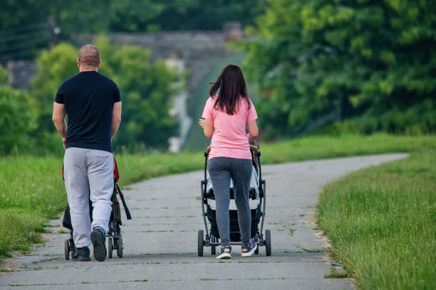 A young couple pushing a baby carriage stock photo