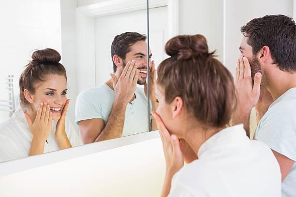 junges paar putting auf face cream - feminine badezimmer stock-fotos und bilder