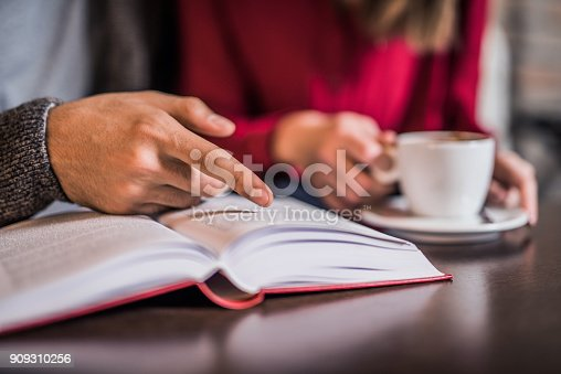 Young couple reading a book in a coffee shop hands only.