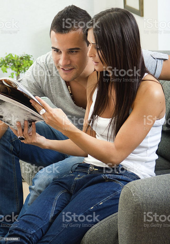A young couple reading a magazine on the sofa royalty-free stock photo