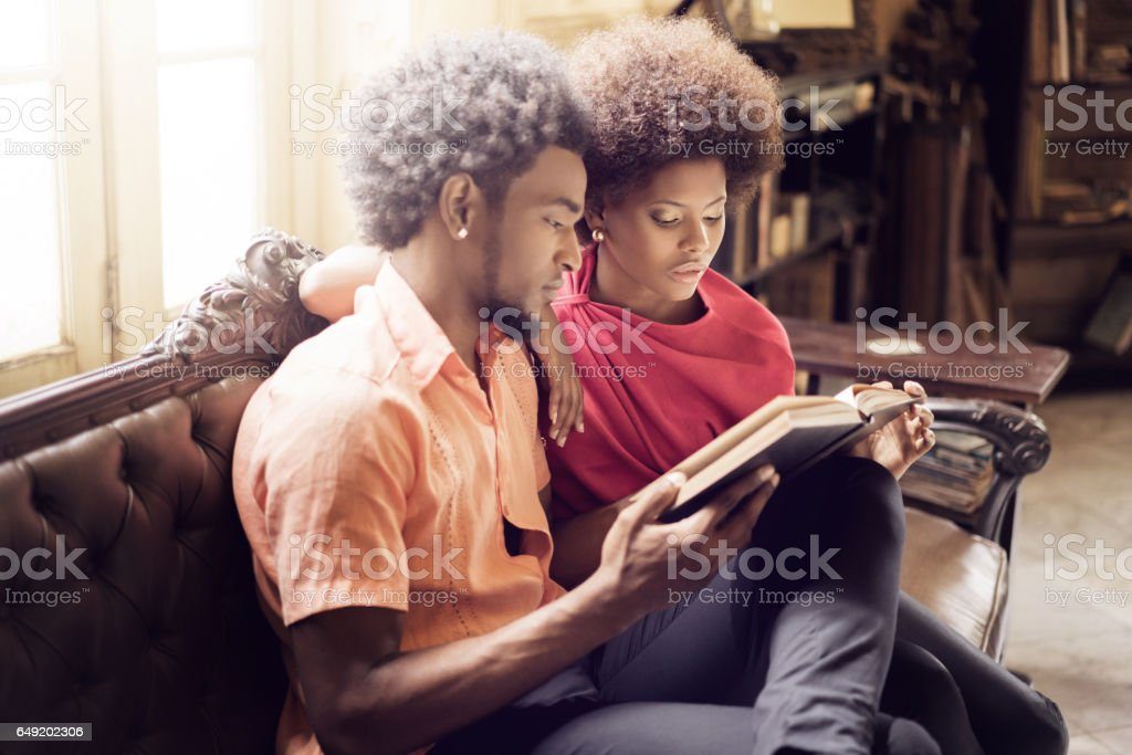 Young couple reading book together stock photo