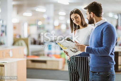 Young couple buying new furniture and reading cataloge in the store. Copy space.